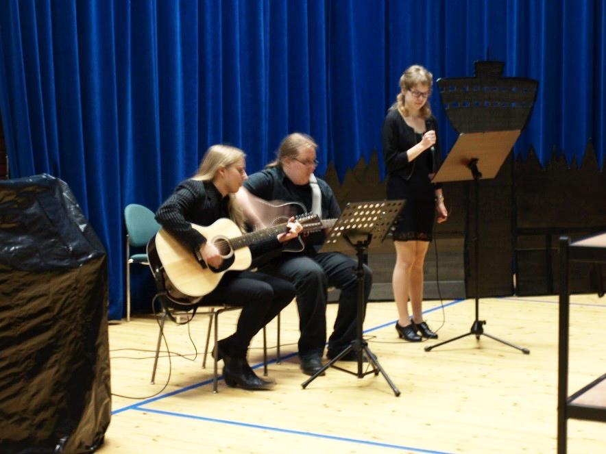 Mia Puustinen laulaa ja kaksi kitaristia säestää