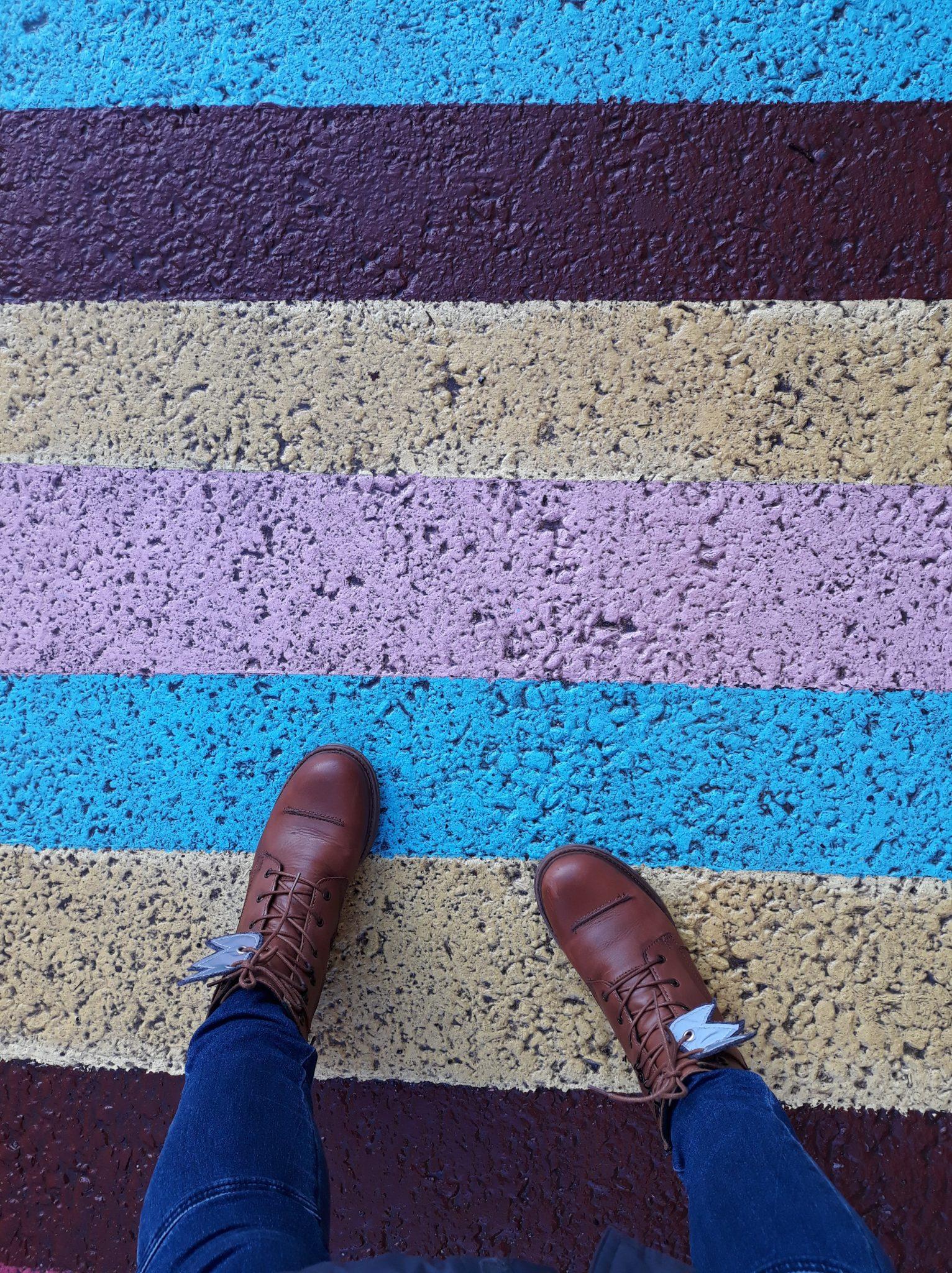 Kengät asvaltilla, jossa on erivärisiä raitoja.