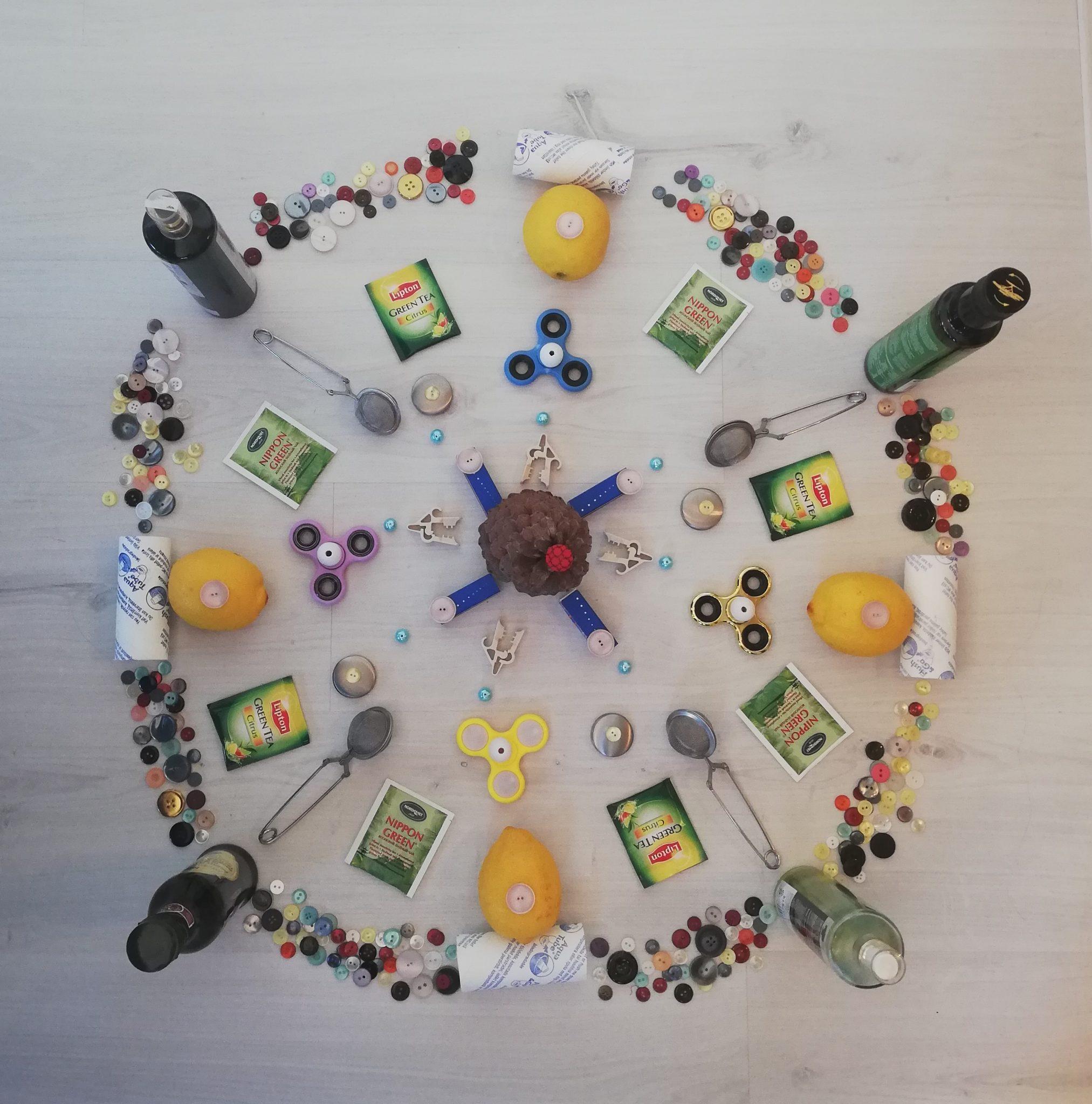Erinäisistä tarvikkeista, kuten napeista, teepusseista ja pulloista tehty ympyrä.